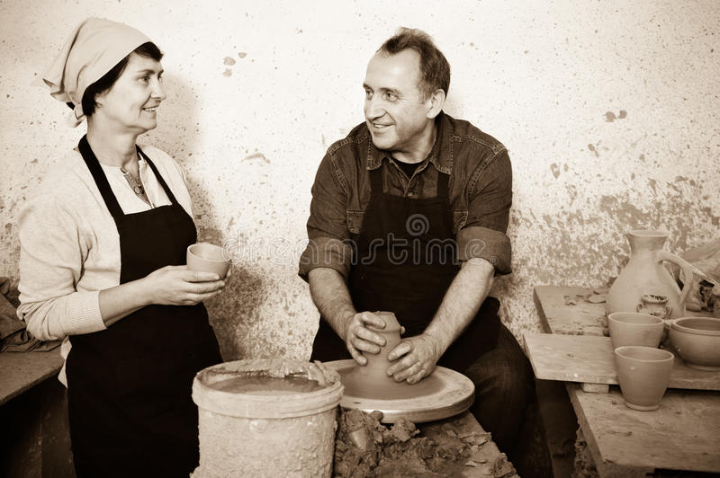 Two potters in the process of work at the workshop. Two pleasant potters in the process of work at the workshop royalty free stock photos