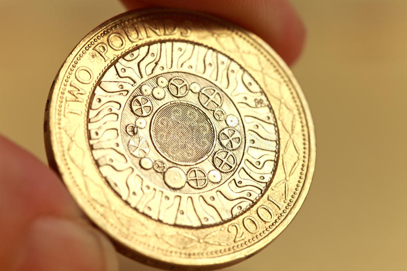 Two pound coin. Back of two pound coin with hand holding stock images