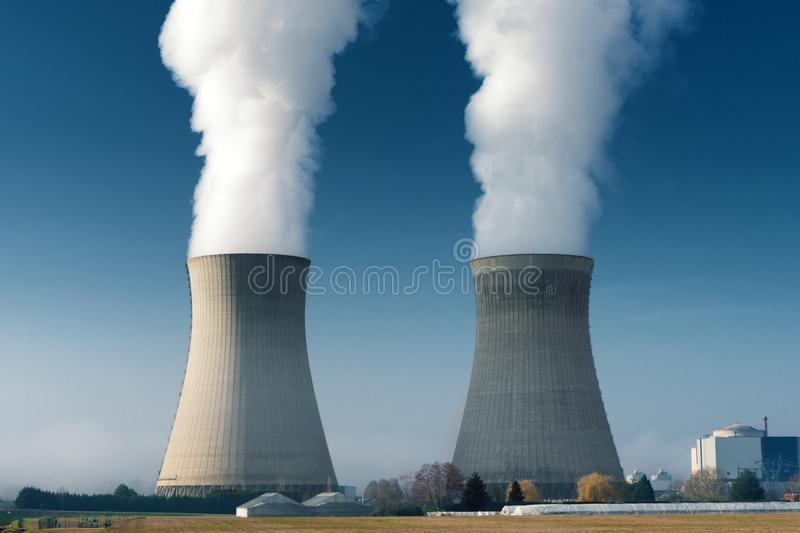 Two power plant cooling towers steaming. On dark blue sky background royalty free stock images