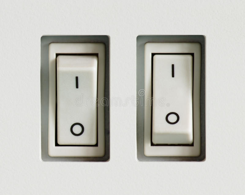 Two power switches built into plastic surface. Two power switches built into gray plastic textured surface is switched on and off stock image