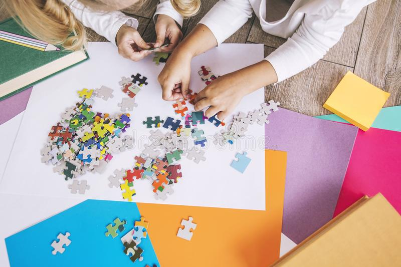 Two preschool age child put the puzzle together on the floor, ha. Nds close up royalty free stock photos