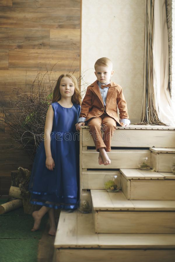 Two preschool children boy and girl sit together at the outdoor in the stock image