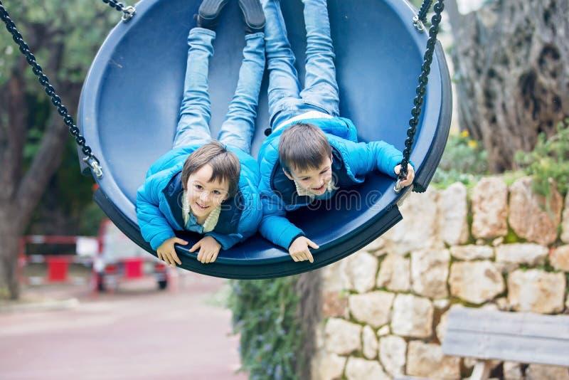 Two preschool children in a swing, having fun. Springtime stock image
