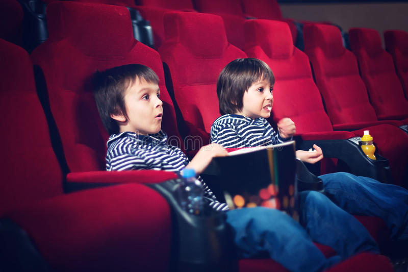 Two preschool children, twin brothers, watching movie in the cinema. Eating popcorn royalty free stock image