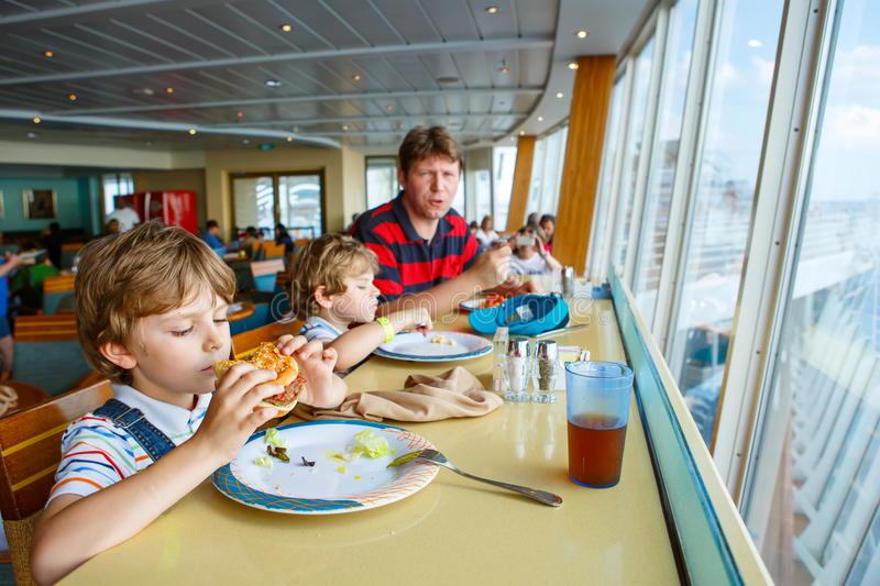 Two preschool kids boys and father eating hamburger sitting in cafe on cruise ship. Two preschool kids and father boys eating pasta hamburger sitting in cafe on royalty free stock image