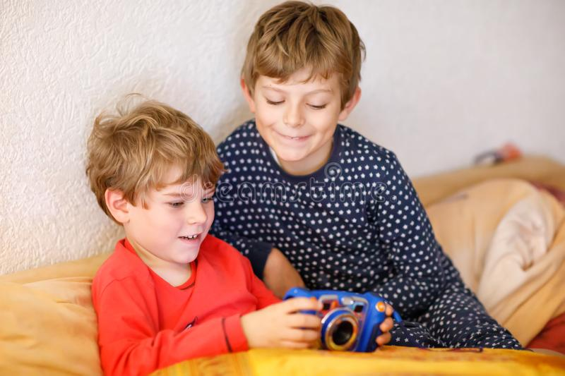 Two preschool or school kids boys, siblings and brothers having fun after school day playing video game at home and stock photo