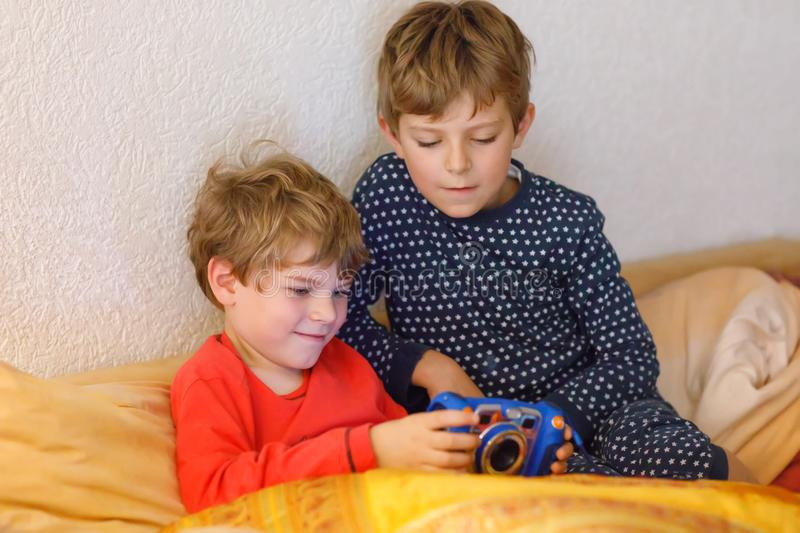 Two preschool or school kids boys, siblings and brothers having fun after school day playing video game at home and. Taking pictures with toy camera. Best stock photos