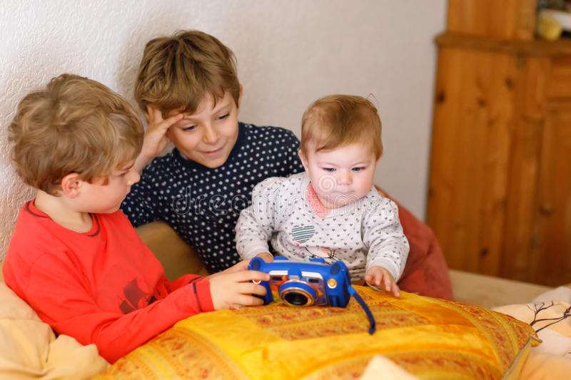 Two preschool or school kids boys, siblings and brothers and little baby girl sister having fun after school day playing. Video game at home and taking pictures stock image