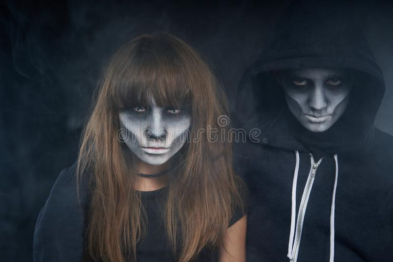 Two preteen kids with zombie makeup. Halloween zombie friends. Two preteen kids with zombie makeup looking at camera over dark background with smoke stock photo