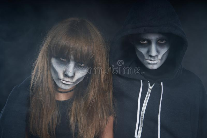 Two preteen kids with zombie makeup. Halloween zombie friends. Two preteen kids with zombie makeup looking at camera over dark background with smoke royalty free stock photo