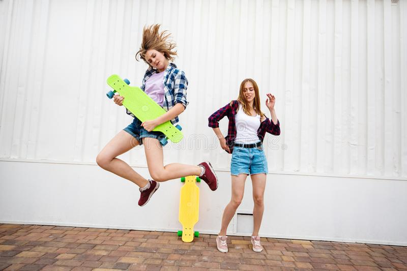 Two pretty blond girls wearing checkered shirts and denim shorts are jumping and dancing with bright longboards. Young royalty free stock photo