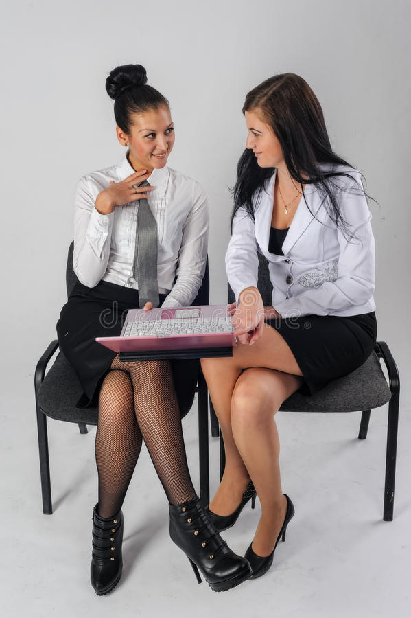 Two pretty business ladies work and smile. Two young attractive businesswomen with laptop smile over white background stock photos