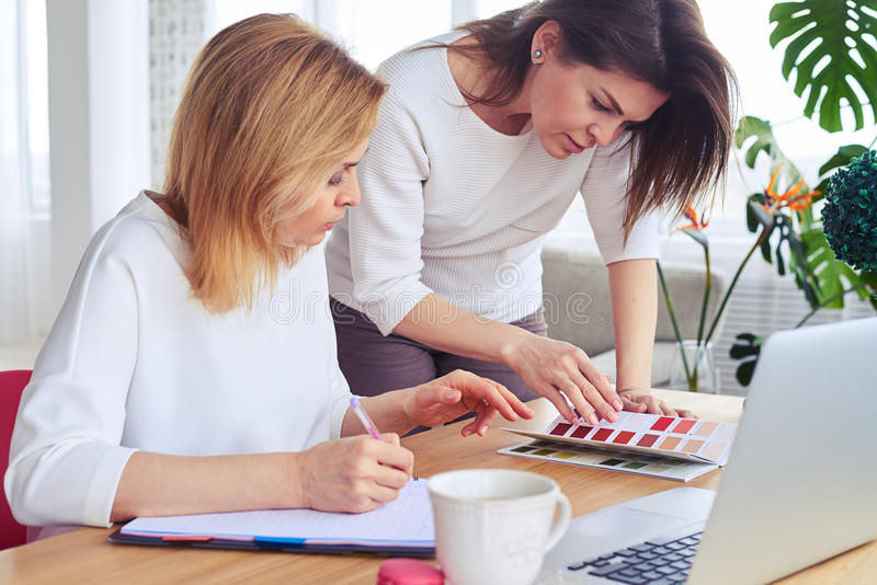 Download Two Pretty Businesswomen Looking Through Catalog Of Color Palett Stock Photo - Image: 92490730