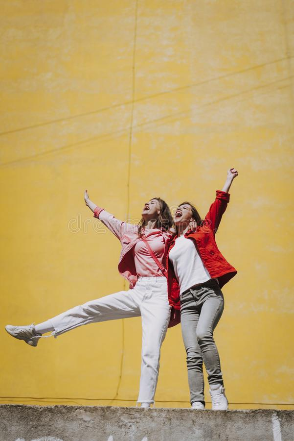 Two pretty cheerful hipster girls enjoying life royalty free stock photography