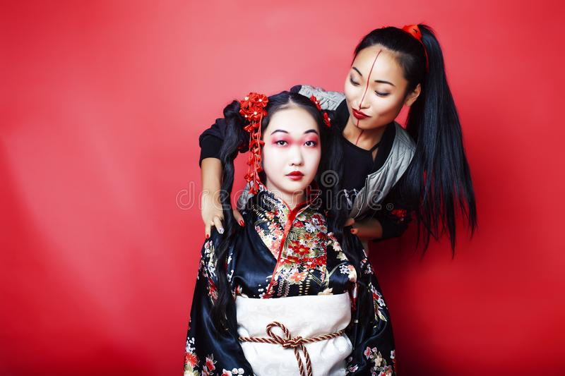 Two pretty geisha girls friends: modern asian woman and traditional wearing kimono posing cheerful on red background. Two pretty geisha girls friends: modern royalty free stock photo