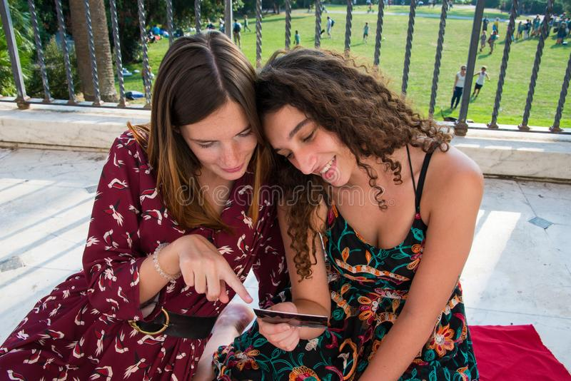 Two pretty girls are choosing photos for social media. royalty free stock photo