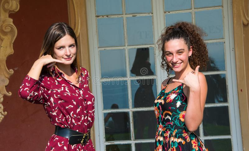 Two pretty girls are doing the call me sign. royalty free stock photos