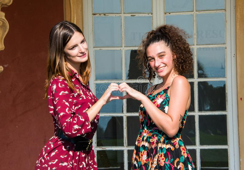 Two pretty girls are doing the heart sign. Two pretty girls are standing against each other and doing the `heart` sign with their hands. They are dressed with stock image