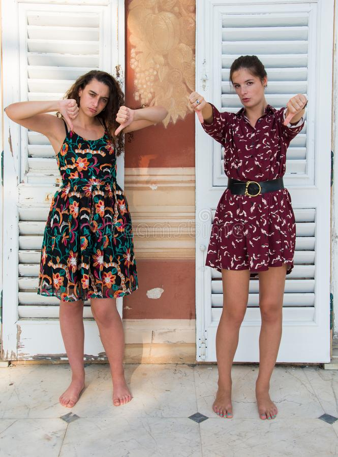 Two pretty girls are doing the thumbs down sign. royalty free stock images