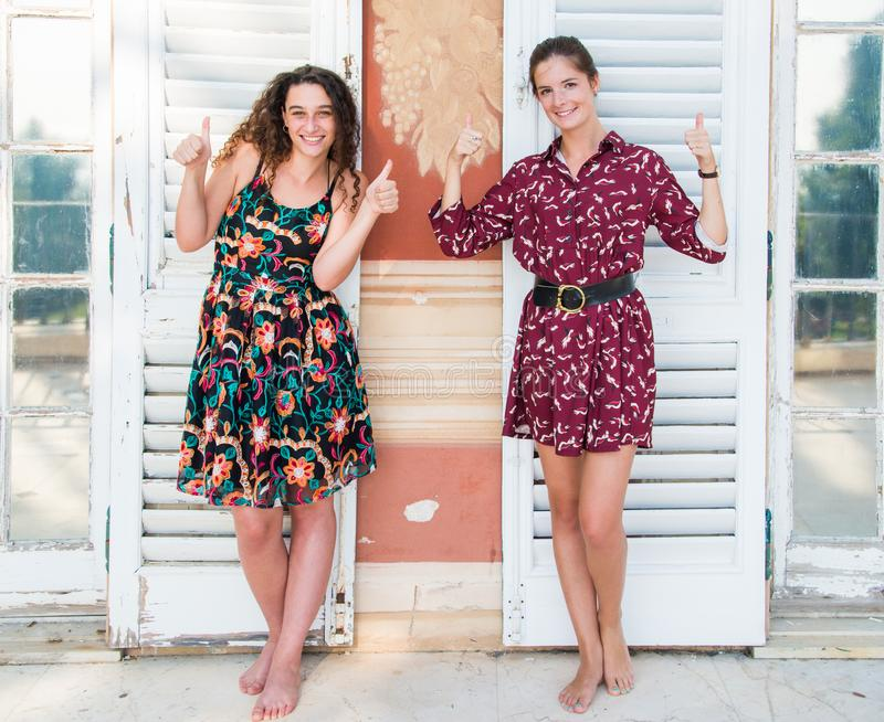 Two pretty girls are doing the thumbs up sign. Two pretty girls are standing next to each other and doing the `thumbs up` sign with their hands. They are stock image