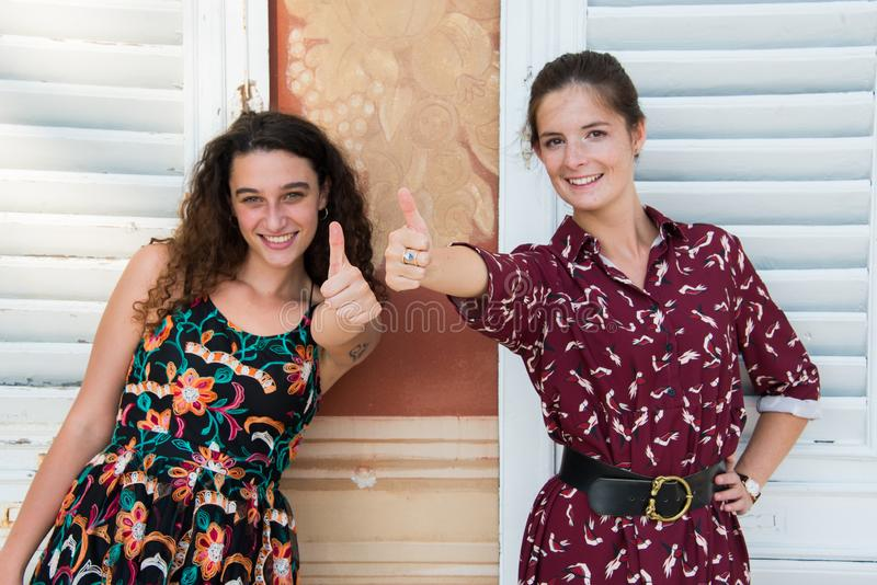 Two pretty girls are doing the thumbs up sign. Two pretty girls are standing next to each other and doing the `thumbs up` sign with their hands. They are stock photos