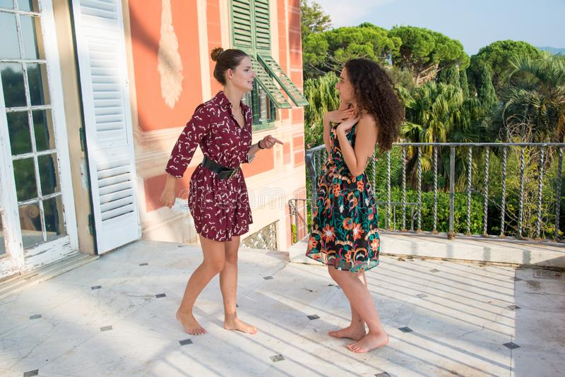 Two pretty girls are fighting over bullshit. Two pretty girls are fighting over a men or job position. They are dressed with colorful dresses and sitting on a stock images