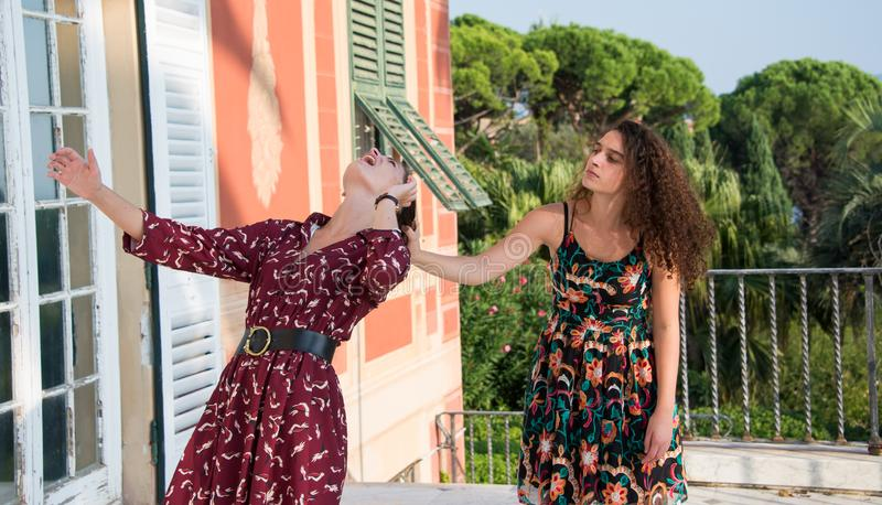 Two pretty girls are fighting and pulling their hair. Two pretty girls are fighting over a men or job position. They are dressed with colorful dresses and stock photography