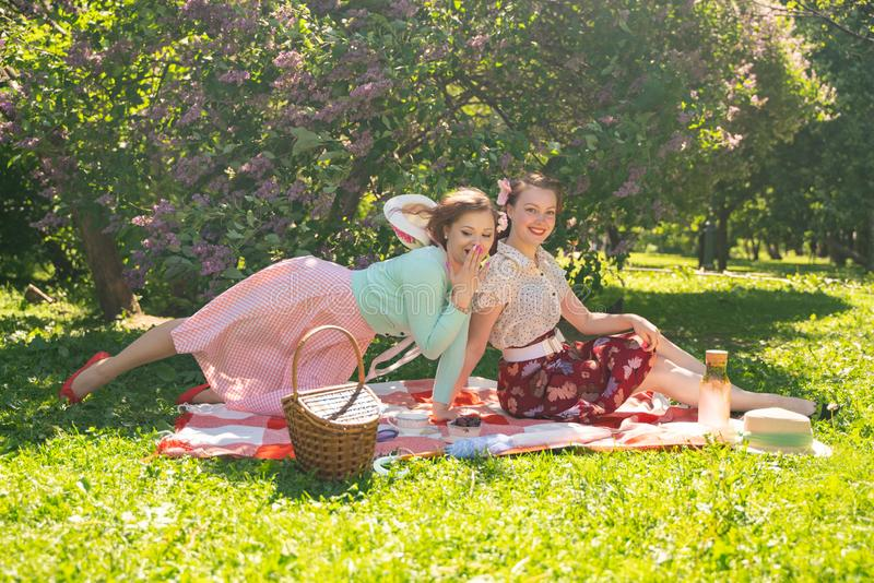 Two pretty girls friends sitting on the red blanket on the green grass and have summer picnic. happy woman having rest and fun on royalty free stock images