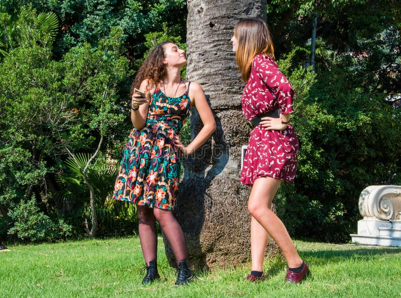 Two pretty girls are gossiping over a facebook profile. Of their friend. Bullying on the internet concept. They are dressed with colorful dresses and sitting on stock image
