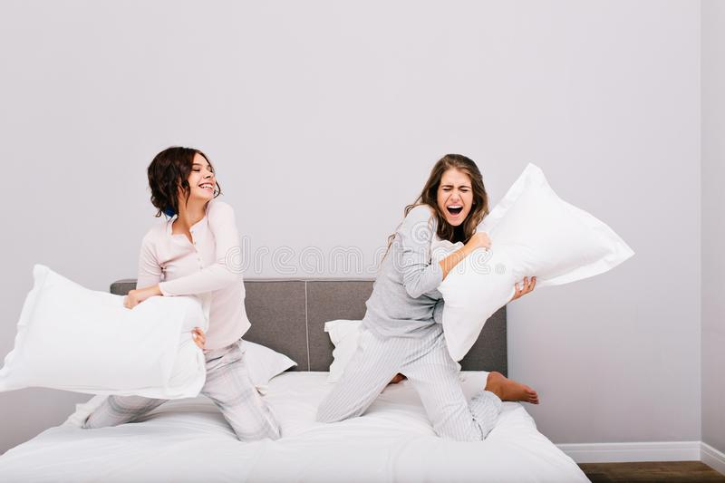 Two pretty girls having pajamas party. They fighting with pillow fight on bed. royalty free stock photo