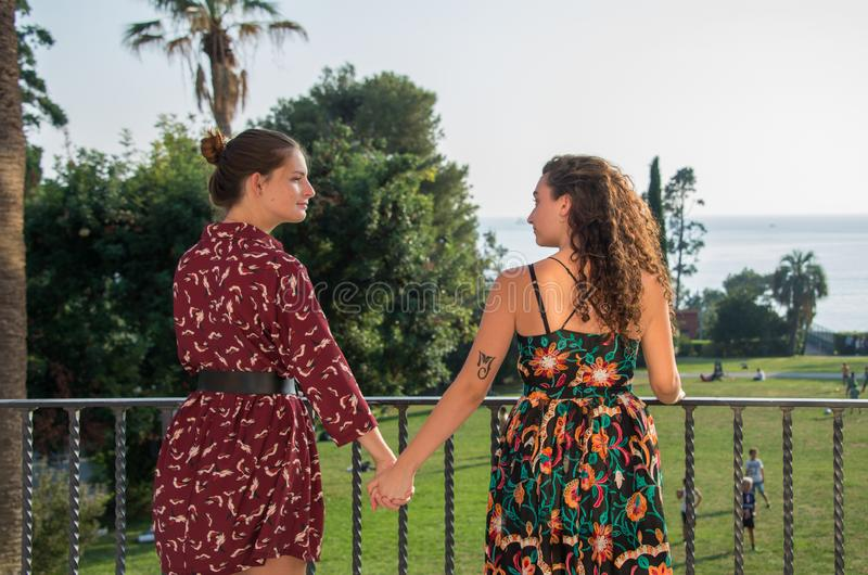 Two pretty girls are holding hands in the beautiful park. Two pretty girls are holding hands for a lesbian concept. Real love between women. They are dressed stock photo