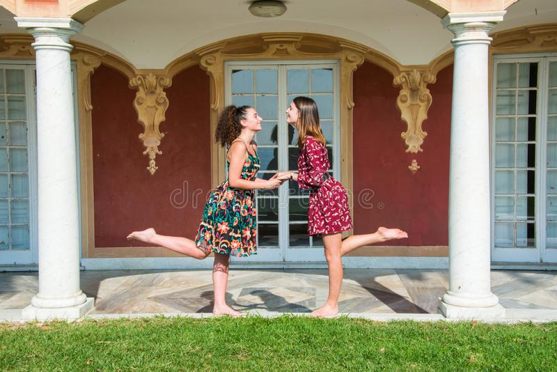 Two pretty girls are are holding hands. Two pretty girls are holding hands and lifting one leg and looking at each other. They are dressed with colorful dresses stock image