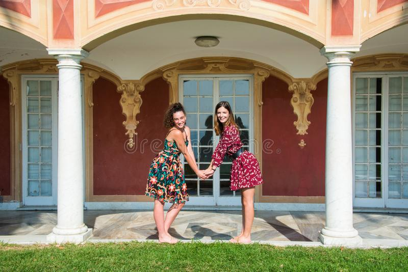 Two pretty girls are are holding hands and looking at camera royalty free stock photography