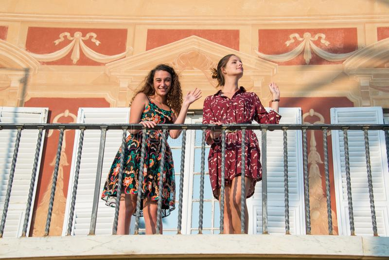 Two pretty girls are looking around and waving from a balcony royalty free stock photos