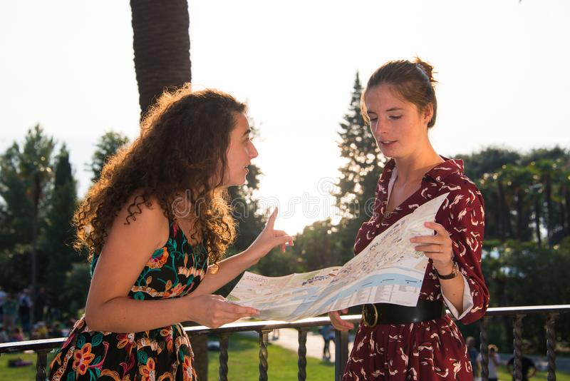 Two pretty girls are looking at a map and looking arround. Two pretty girls are looking and thinking at a map and searching for a destination. Tourist concept stock photography