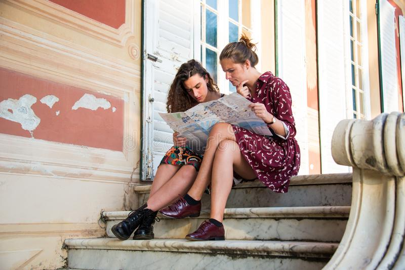 Two pretty girls are looking at a map on stairs. Two pretty girls are looking and thinking at a map and searching for a destination. Tourist concept. They are stock images