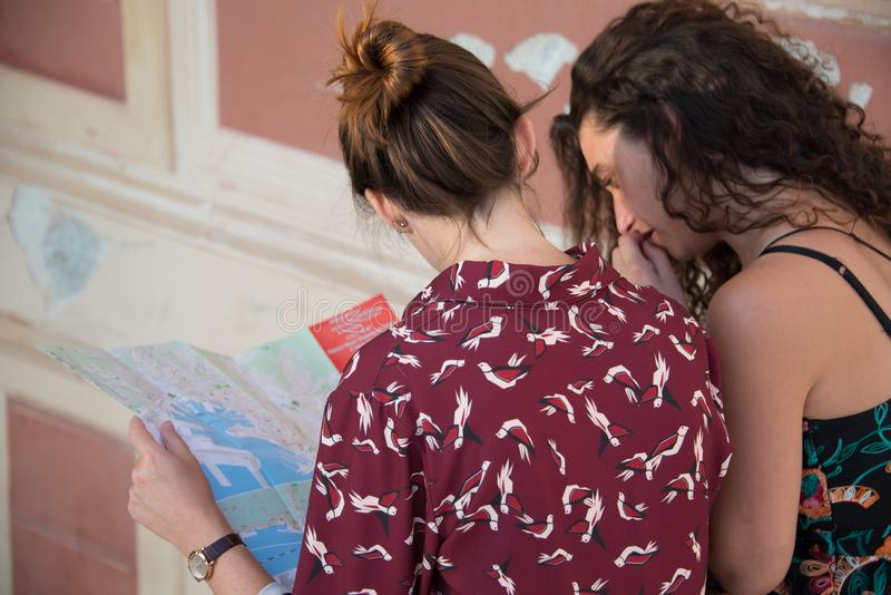Two pretty girls are looking at a map on stairs. Two pretty girls are looking and thinking at a map and searching for a destination. Tourist concept. They are royalty free stock image