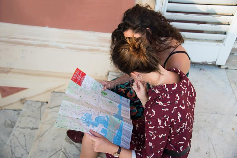 Two pretty girls are looking at a map on stairs. Two pretty girls are looking and thinking at a map and searching for a destination. Tourist concept. They are royalty free stock images