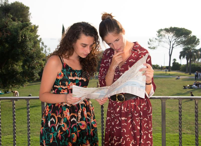 Two pretty girls are looking at a map and looking arround. Two pretty girls are looking and thinking at a map and searching for a destination. Tourist concept stock image