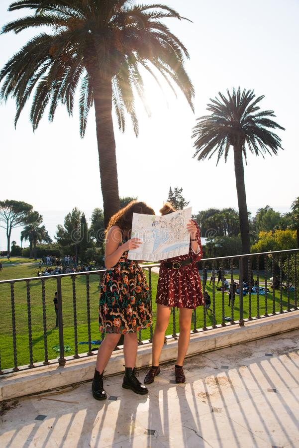 Two pretty girls are looking at a map and looking arround. Two pretty girls are looking and thinking at a map and searching for a destination. Tourist concept stock photo