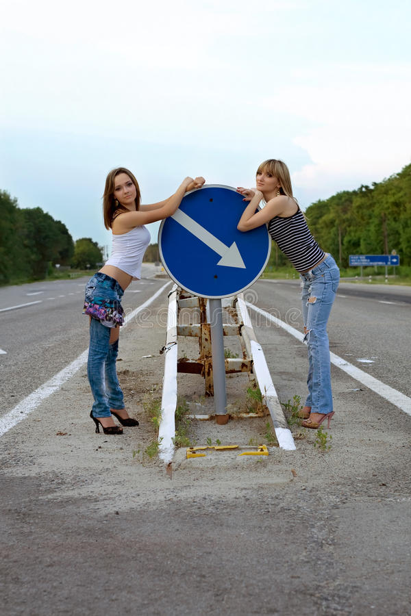 Two pretty girls stand on a road stock images