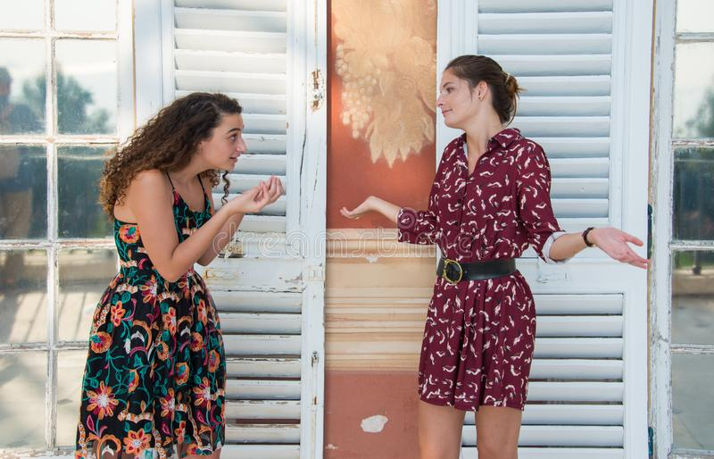 Two pretty girls are doing the Italian what are you talking about? sign. royalty free stock photography