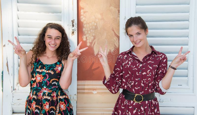 Two pretty girls are doing the peace sign. royalty free stock photography