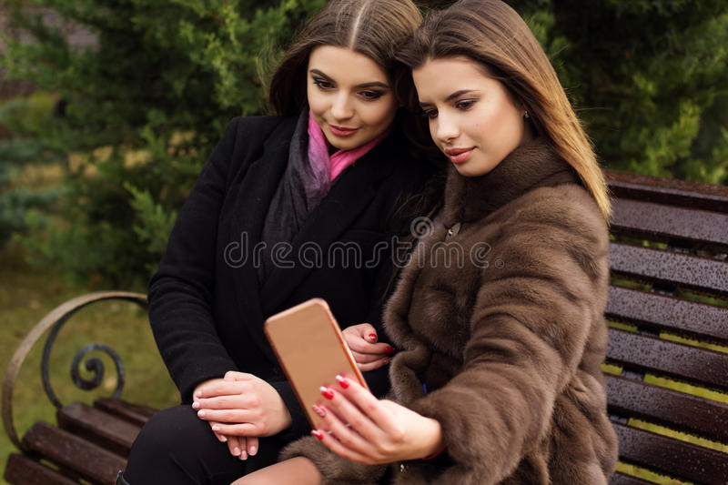 Two pretty girls are taking selfie with smartphone. Two beautiful friends girls are wearing warm winter coats posing and taking selfie with smartphone outdoors stock photo