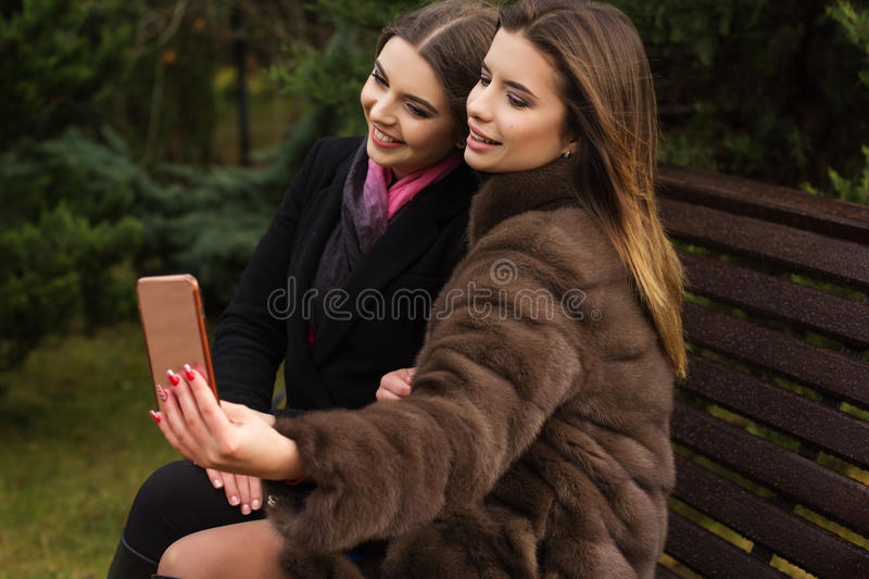 Two pretty girls are taking selfie with smartphone. Two beautiful friends girls are wearing warm winter coats posing and taking selfie with smartphone outdoors stock images