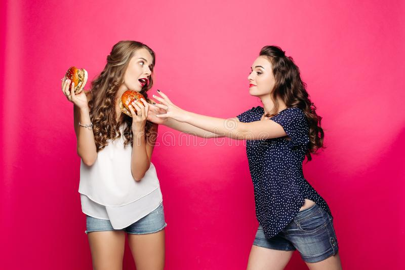 Two pretty and hungry girls wanting two big hamburger. stock image