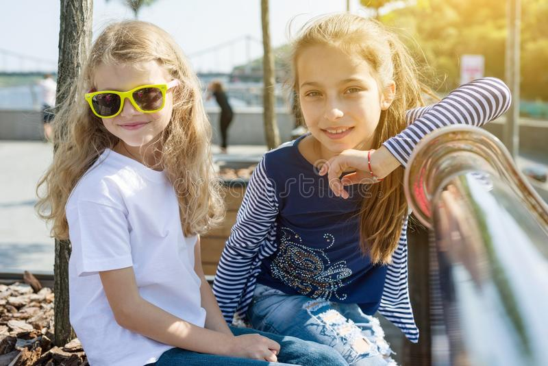 Two pretty little girls are looking at the camera and smiling. royalty free stock photos