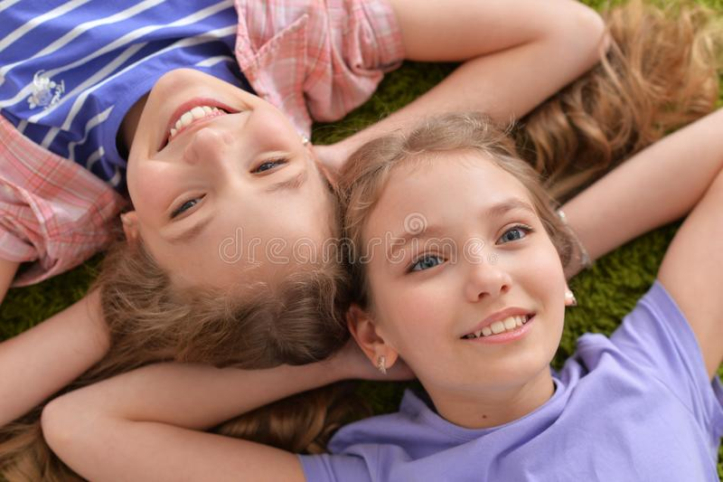 Portrait of two pretty little girls lying on green carpet and looking at camera stock image