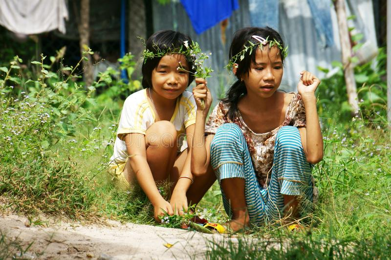 Two pretty little girls picking wild flower to make head wreath at grassland in summertime stock images