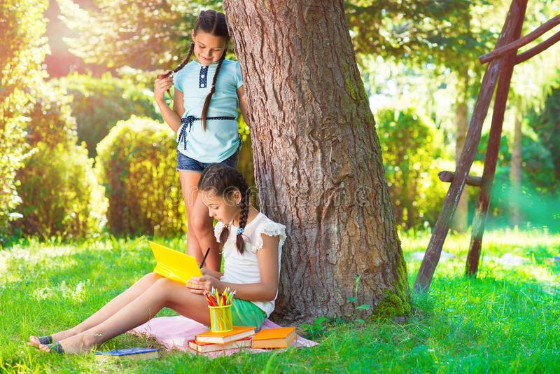 Two pretty little girls reading in park royalty free stock photo